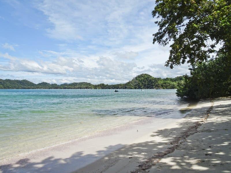 Baia pittoresca con una spiaggia sabbiosa con la sabbia leggera sotto un cielo blu con le nuvole immagine stock libera da diritti