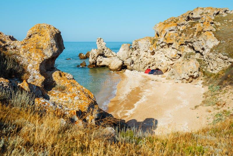 Baia selvaggia del mare nelle rocce con tre tende Spiaggia di sabbia fotografia stock libera da diritti