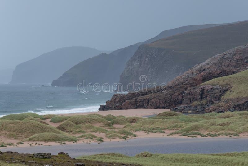 Baie de Sandwood, montagnes de l'Ecosse Baie à distance avec le sable, les dunes et les roseaux blancs Situé sur la côte écossais image libre de droits