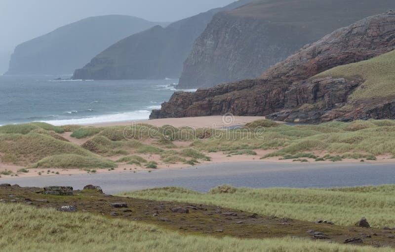 Baie de Sandwood, montagnes de l'Ecosse Baie à distance avec le sable, les dunes et les roseaux blancs Situé sur la côte écossais photos libres de droits