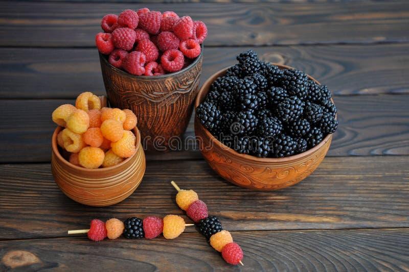 Baies colorées des framboises rouges, jaunes et noires ou des mûres en poterie de terre sur une table photo libre de droits