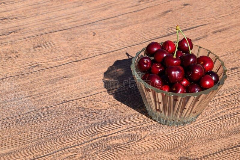 Baies d'une merise dans un bol en verre sur un fond en bois Bonbon rouge mûr photo stock