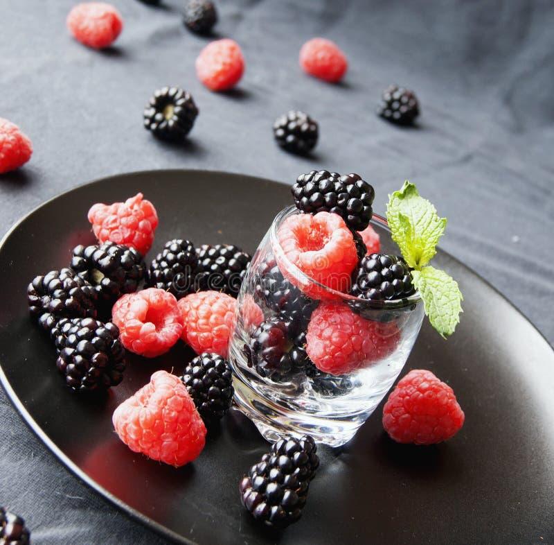 Baies et framboises noires dans une tasse en verre photographie stock