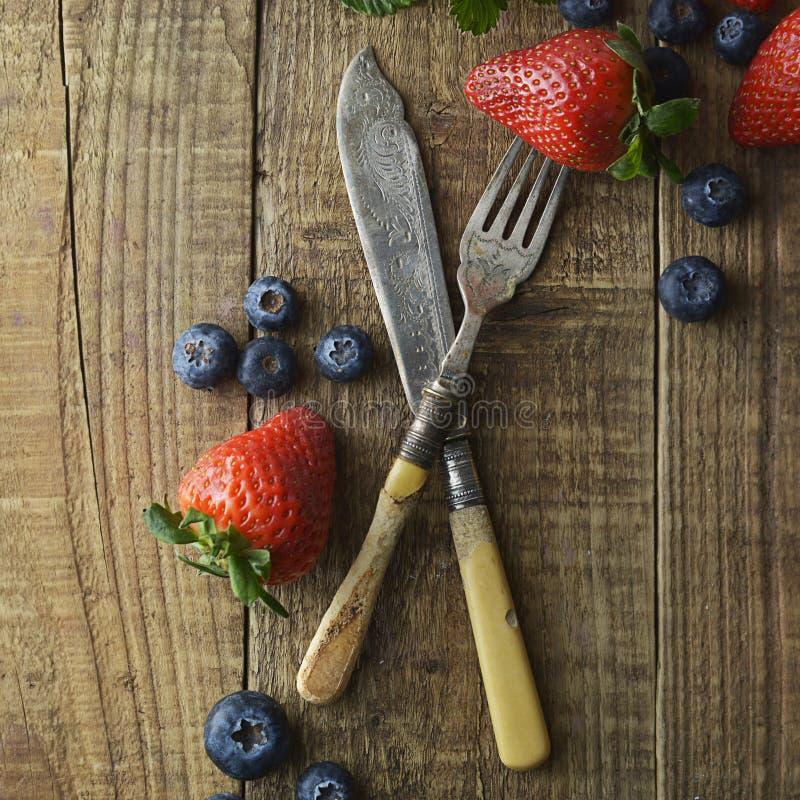 Baies mélangées, myrtille, fraise sur le fond en bois avec le cru, fourchette dénommée et couteau Nourriture dénommée, fond de fr images libres de droits