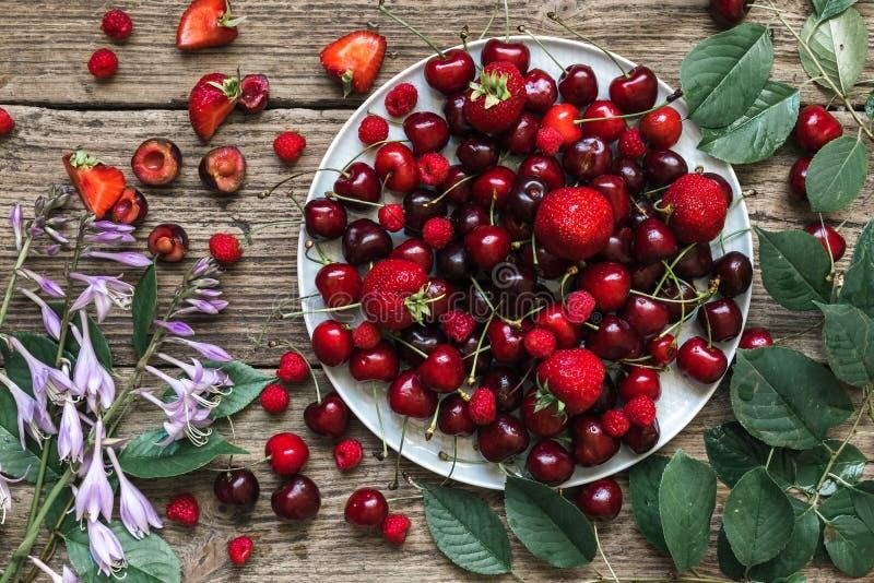 Baies rouges mûres fraîches - cerise, fraise et framboise d'un plat avec des fleurs d'été sur le fond en bois rustique image libre de droits