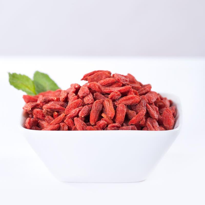 Baies sèches rouges de goji dans une cuvette photo stock