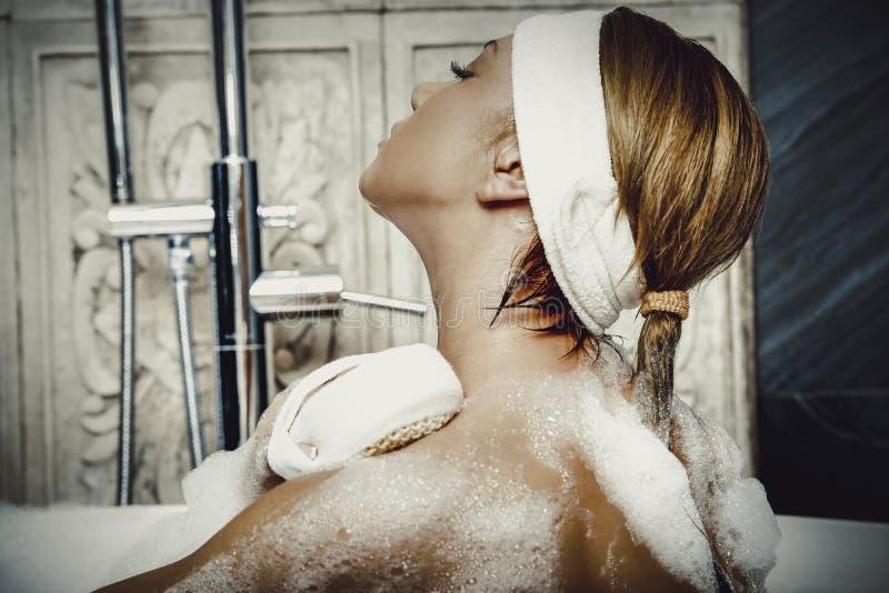Baignant la femme la nettoyant de retour avec du savon image libre de droits