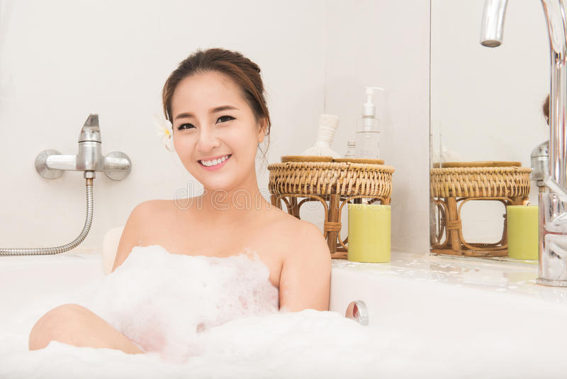 Baigner la femme détendant dans la détente de sourire de bain Jeune femme asiatique dans la baignoire image libre de droits