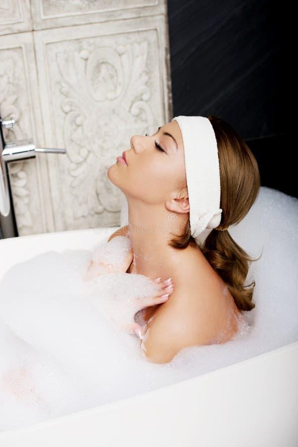 Baigner la femme détendant dans le bain photographie stock libre de droits