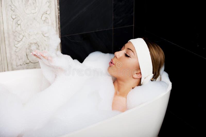 Baigner la femme détendant dans le bain photographie stock