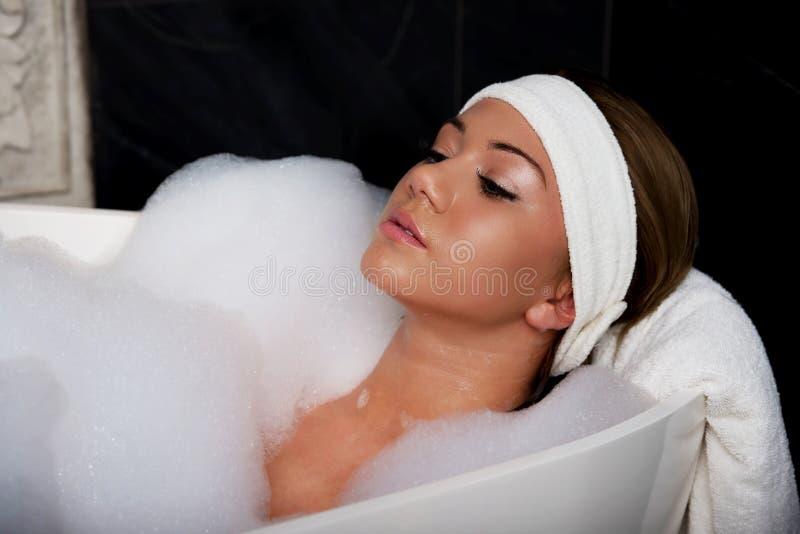 Baigner la femme détendant dans le bain images libres de droits