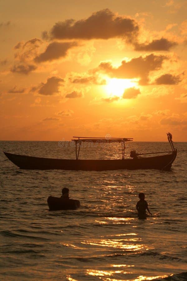 Baigneurs de coucher du soleil à la plage de hasard heureux image libre de droits
