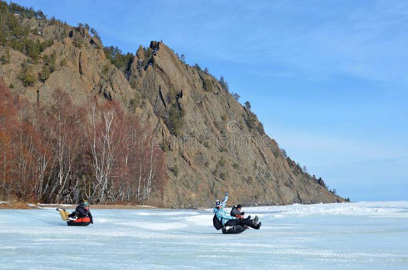 Baikal lake, Russia, March, 01, 2017. Tourists riding on a sled sledges MS icy shores of lake Baikal stock image