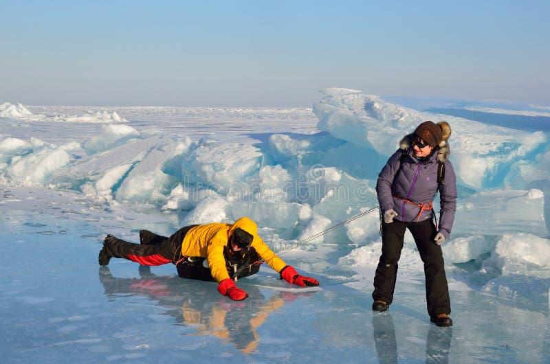 Baikal See, Russland, März, 01, 2017 Touristen ziehen sich auf einem Schlitten vor den Eiskanten nahe dem Dorf der Bolschewik Ko lizenzfreie stockfotografie