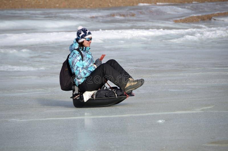 Baikal sjö, Ryssland, mars, 01, 2017 Ridningen för den unga kvinnan på en släde åka släde iskalla kuster för ms av Lake Baikal arkivfoton