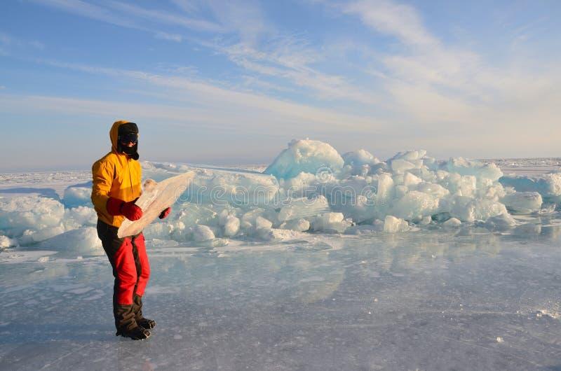 Baikal sjö, Ryssland, mars, 01, 2017 Turist i en skidamaskering med ett kvarter av is i händerna på vintern Baikal fotografering för bildbyråer