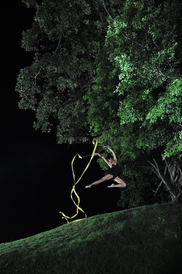 Bailado asiático da dança da menina sob a árvore grande na noite imagens de stock royalty free