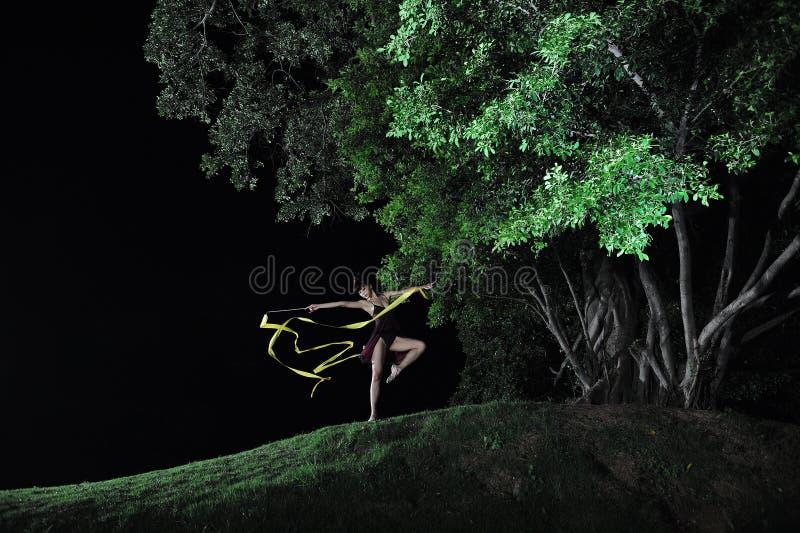 Bailado asiático da dança da menina sob a árvore grande na noite fotografia de stock royalty free