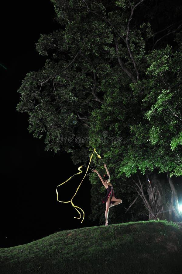 Bailado asiático da dança da menina sob a árvore grande na noite foto de stock