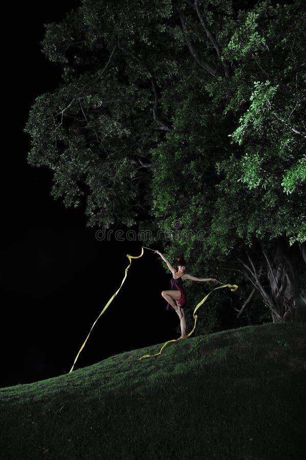 Bailado asiático da dança da menina sob a árvore grande na noite imagens de stock