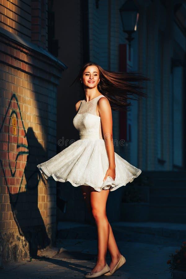 Bailan a la mujer joven en un vestido blanco corto en una danza en una calle abandonada en un fondo de la pared Ella está bailand imagen de archivo libre de regalías