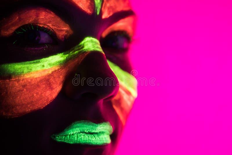 Bailarín atractivo de la moda en la luz de neón Maquillaje fluorescente que brilla intensamente bajo luz ultravioleta Club noctur fotos de archivo