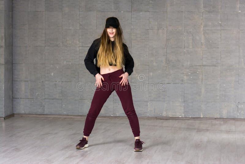Bailarín casual de la muchacha que presenta en fondo gris imagenes de archivo