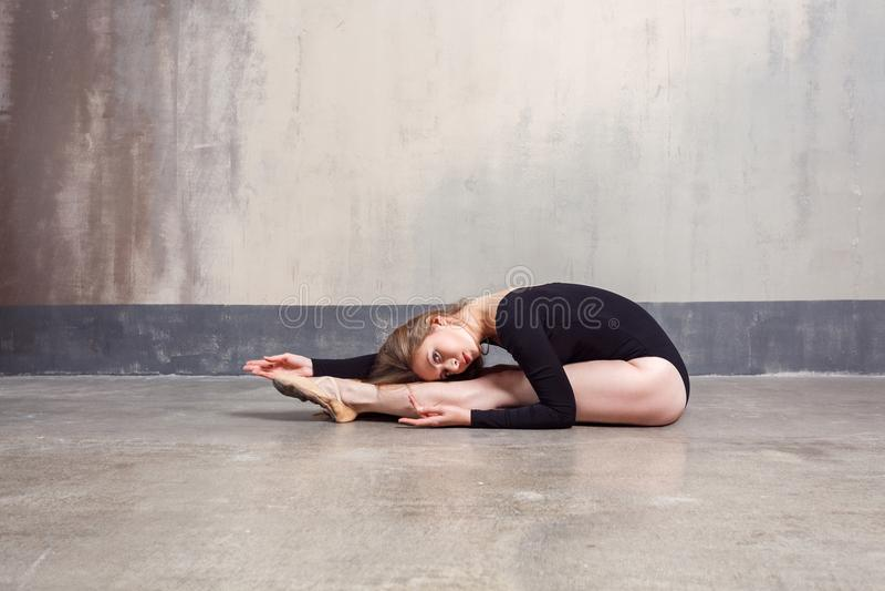 Bailarín de ballet adulto joven que realiza ejercicio mientras que se sienta en f imagenes de archivo