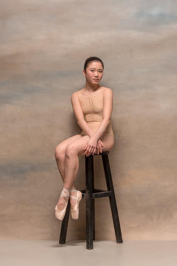 Bailarín de ballet cansado que se sienta en la silla de madera en un fondo rosado imágenes de archivo libres de regalías