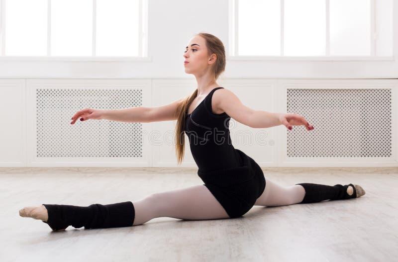 Bailarín de ballet clásico que estira en la clase de entrenamiento blanca foto de archivo