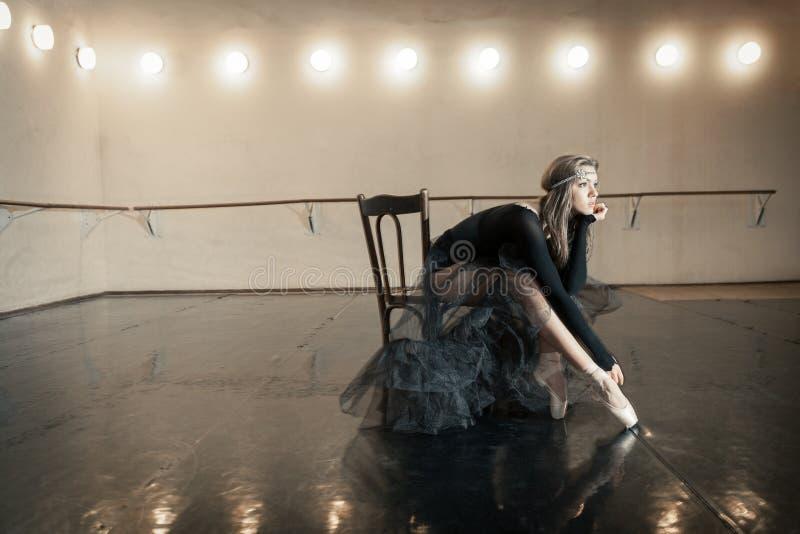 Bailarín de ballet contemporáneo en una silla de madera en una repetición foto de archivo
