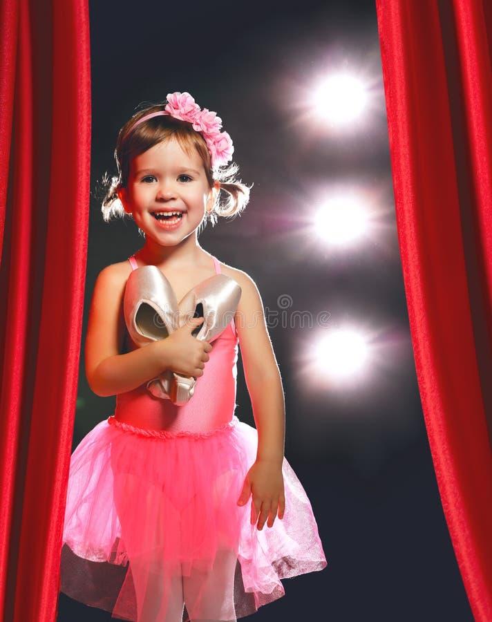 Bailarín de ballet de la bailarina de la niña en etapa en escenas laterales rojas foto de archivo