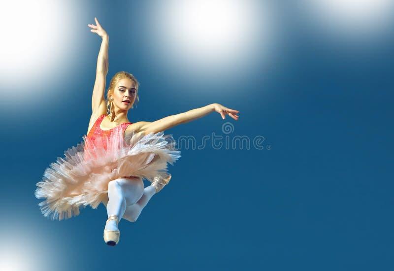 Bailarín de ballet de sexo femenino hermoso en un fondo gris La bailarina está llevando los zapatos rosados del tutú y del pointe fotos de archivo libres de regalías