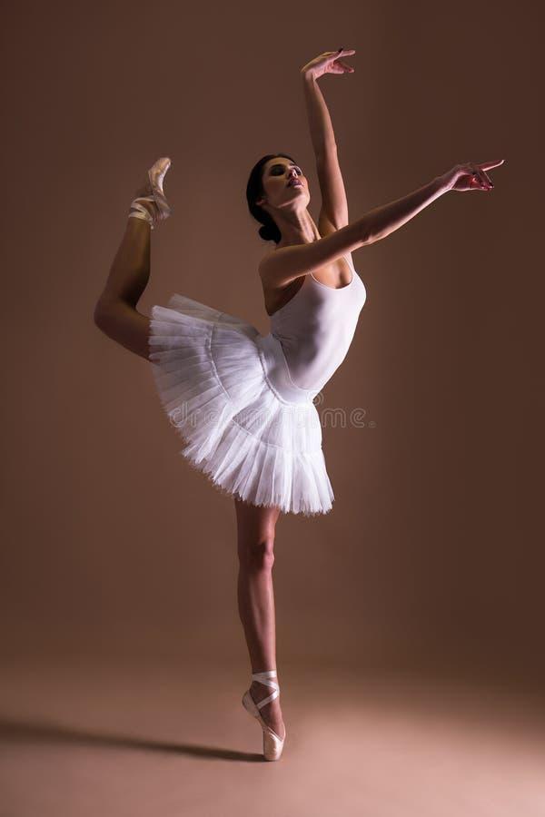 Bailarín de ballet hermoso joven de la mujer en el tutú que presenta en los dedos del pie encima imagen de archivo libre de regalías