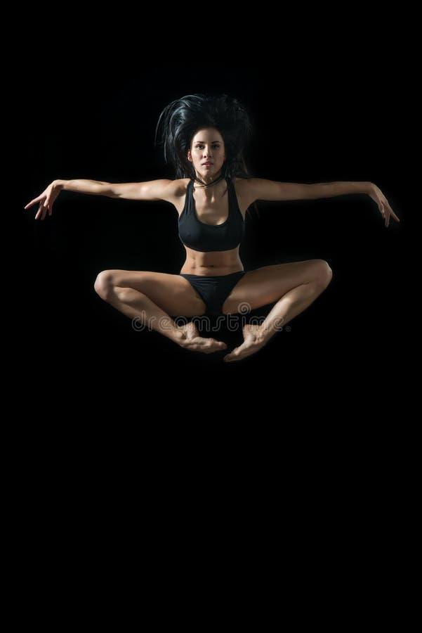 Bailarín de ballet joven dansing en fondo negro fotografía de archivo