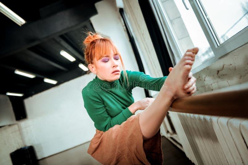 Bailarín de ballet profesional joven con el bollo del pelo que hace estirar de la pierna imagen de archivo