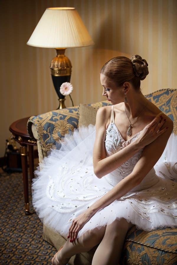 Bailarín de ballet profesional que se sienta en el sofá imagen de archivo libre de regalías