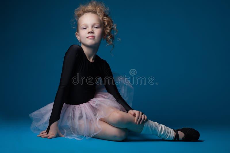 Bailarín de ballet rizado lindo que presenta en fondo azul foto de archivo libre de regalías