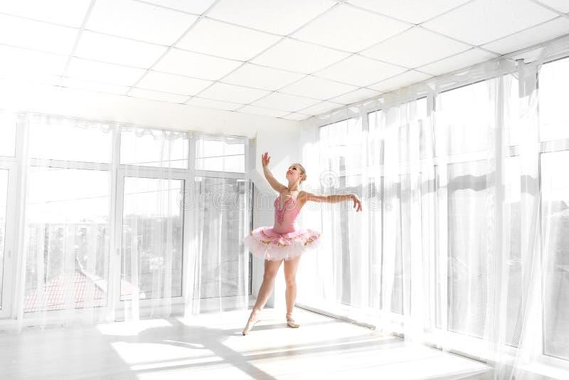 Bailarín de ballet de sexo femenino elegante en el tutú rosado que practica y que sonríe fotografía de archivo