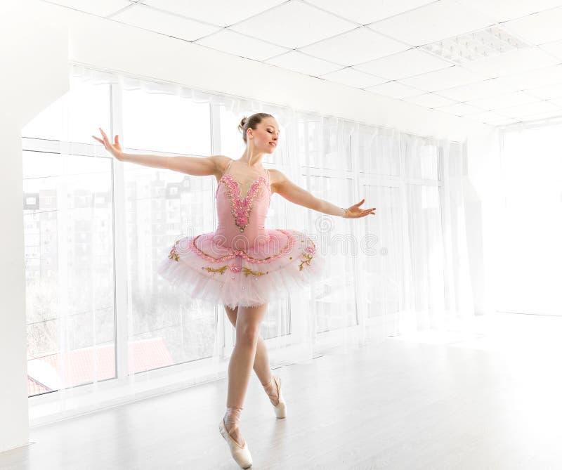Bailarín de ballet de sexo femenino elegante en el tutú rosado que practica y que sonríe foto de archivo libre de regalías