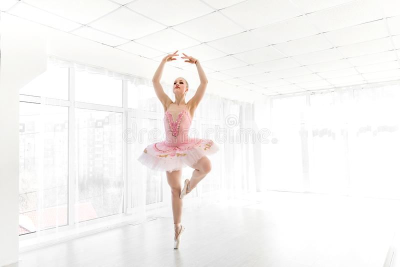 Bailarín de ballet de sexo femenino elegante en el tutú rosado que practica y que sonríe fotografía de archivo libre de regalías