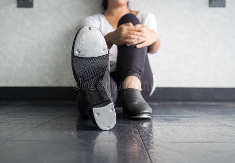 Bailarín de golpecito que se sienta en la clase del golpecito que lleva a cabo una de sus piernas foto de archivo libre de regalías