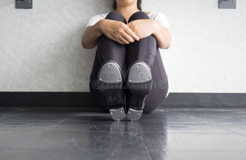Bailarín de golpecito que se sienta, mostrando golpecitos, y llevando a cabo sus piernas imagen de archivo