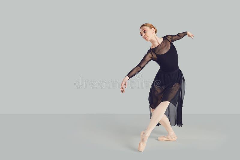 Bailar?n de la bailarina en vestido negro en un fondo gris fotos de archivo libres de regalías