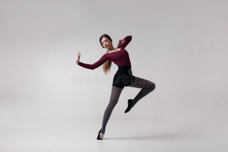 Bailarín de la mujer joven en la presentación marrón del traje de baño fotografía de archivo