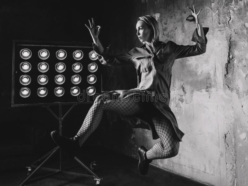 Bailarín de la mujer que salta arriba en el desván fotografía de archivo libre de regalías