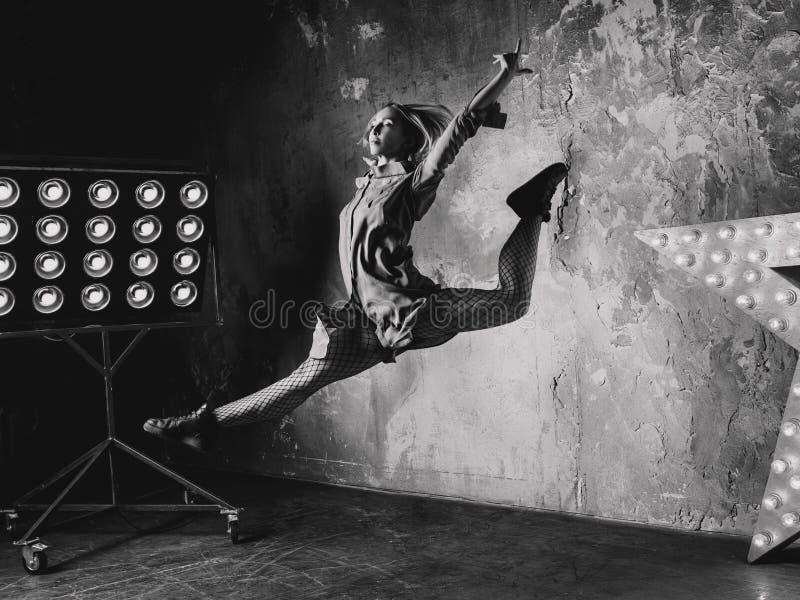 Bailarín de la mujer que salta arriba en el desván foto de archivo libre de regalías
