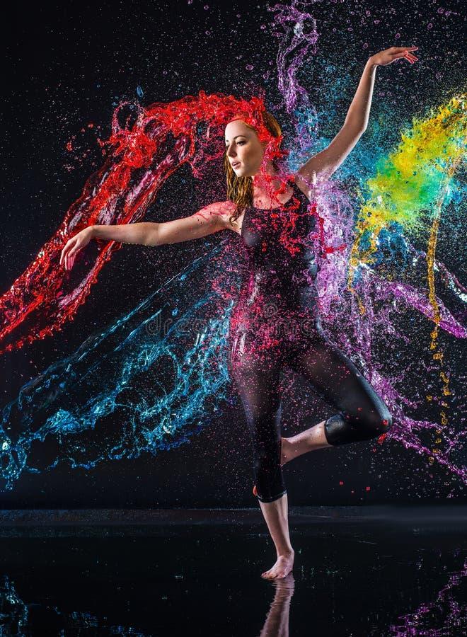 Bailarín de sexo femenino Being Splashed con agua colorida imagen de archivo