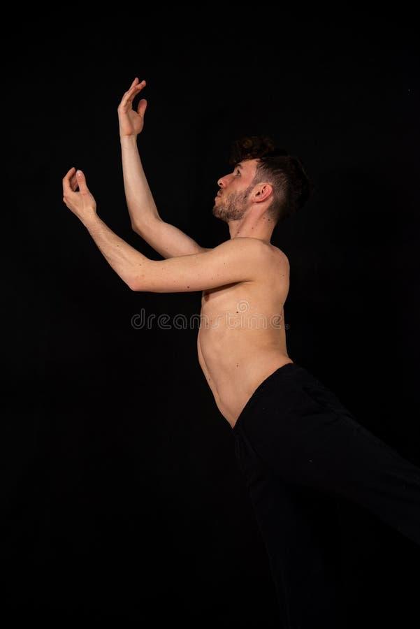 Bailarín de sexo masculino con los pantalones negros y el pecho desnudo, practicando en el estudio en un fondo negro fotos de archivo libres de regalías