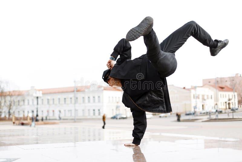 Bailarín de sexo masculino elegante deportivo joven en vaqueros negros en una chaqueta elegante en un casquillo en gafas de sol e foto de archivo